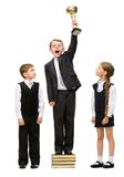 Boy standing with gold cup at pile of books among other children. Full-length portrait of little boy standing with gold cup at pile of books among other children stock image