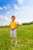 Boy standing on green grass holding his hands Stock Photo
