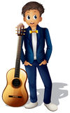 A boy standing beside the guitar Royalty Free Stock Photography