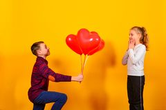 A boy standing on his knee gives the girl a bunch of red balloons in the shape of a heart, on a dark yellow background for