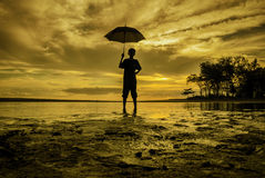 Boy standing holding an umbrella during sunset sunrise Royalty Free Stock Image