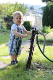 Boy standing by hose pipe installation in the garden. Little kid standing by hose pipe installation in the garden stock images