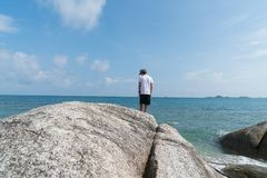 Boy standing on large rock on water`s edge on Bang Kao beach Ko. Boy rear view standing on large rock on water`s edge on Bang Kao beach Ko Samui Stock Image