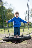 Boy standing on a large swing. Royalty Free Stock Photo