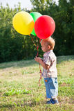 A boy is standing on a lawn with colorful balloons Stock Photography