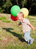A boy is standing on a lawn with colorful balloons Stock Photo