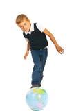 Boy standing with legs on world globe Stock Photo