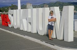 Boy is standing at letters with name of city Sukhumi stock photo