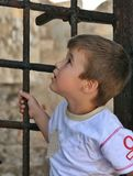 Boy standing and looking up behind an old iron gate on greek cas. Tle Royalty Free Stock Photography