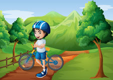 A boy standing in the middle of the pathway with his bike Royalty Free Stock Images