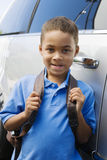 Boy Standing By Minivan. Portrait of schoolboy with backpack standing by minivan Stock Photos