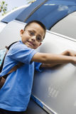 Boy Standing By Minivan. Portrait of Hispanic Latin schoolboy standing by minivan Royalty Free Stock Photography