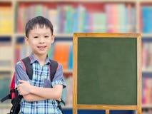 Boy standing near by chalkboard. Happy Asian boy standing near by empty chalkboard in library Stock Photo