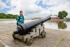 Boy standing near an old cannon in Kronstadt, Russia Royalty Free Stock Image