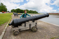 Boy standing near an old cannon in Kronstadt, Russia Stock Photography