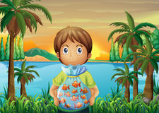 A boy standing near the riverbank while holding a plastic of fis Stock Images