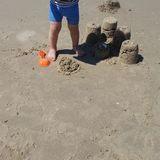 A Boy Standing Near The Sand Towers That He Built With His Plastic Toys At The Beach stock image