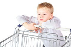 Boy is standing near shoping basket and looking Royalty Free Stock Image