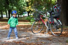 Boy standing next to bicycle in autumn / fall royalty free stock images