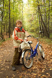 Boy standing next to bicycle in autumn park stock photography