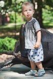 Boy standing next to large metal figure of rhinoceros beetle Royalty Free Stock Image