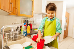 Boy standing next to the sink and wiping dry plate. Portrait of six years old boy standing next to the sink and wiping dry plate with red cloth Stock Photos