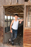 Boy standing at old barn Stock Photography