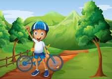 A boy standing in the pathway with his bike Royalty Free Stock Photography