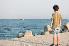 The boy is standing on the pier. Royalty Free Stock Photo