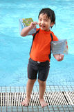 Boy standing by the pool. Boy with arm floats & swimming costumes standing by the pool royalty free stock photos