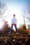 Boy standing between railroad tracks Royalty Free Stock Photos
