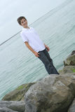 Boy standing on rocks at the beach stock images