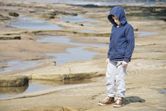 Boy standing on rocks. Young boy in blue jacket standing on rocks and exploring at the seaside. Taken in Whitley Bay in the North East of the UK royalty free stock image