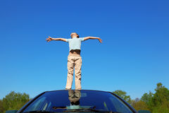 Boy standing on roof of car, opening hands Stock Photos