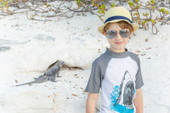 Boy standing on sand background with iguana Stock Photography