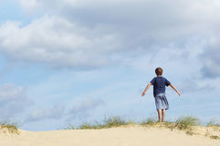 Boy Standing On Sand At Beach With Arms Out Stock Image