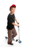 Boy standing beside a scooter Stock Photo
