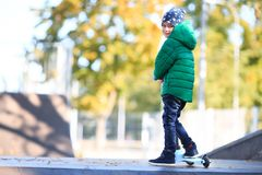 The boy is standing with a scooter in the park. Outside. A little boy in a green jacket and jeans walks with a scooter in the park. Outside Stock Photo