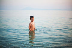 Boy standing in shallow water Royalty Free Stock Photos