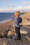 Boy standing on shore wiping his tears royalty free stock images