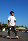Boy Standing on a Skateboard Stock Images