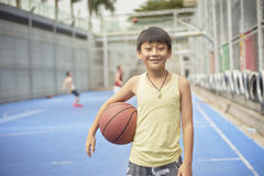 Boy standing smiling at camera with basketball Royalty Free Stock Photography