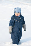 Boy standing on the snow field Royalty Free Stock Photos