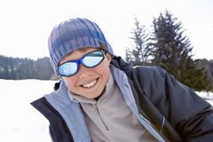 Boy (7-9) standing in snow field, wearing sunglasses, smiling, portrait Stock Images