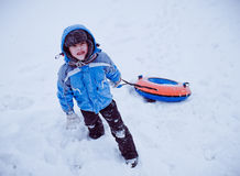 The boy standing in the snow , holding the tubing Royalty Free Stock Photos