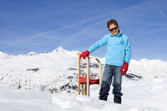 Boy (7-9) standing in snow by sled, wearing sunglasses, smiling, portrait, mountain range in background Royalty Free Stock Image