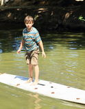 Boy standing on surf Stock Photo