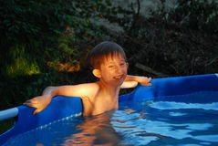 Boy standing in swimming pool laughs Stock Images
