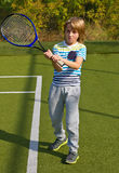 Boy standing with tennis racket and ball on the court Stock Images