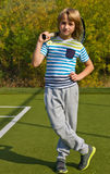 Boy standing with tennis racket and ball on the court Royalty Free Stock Image